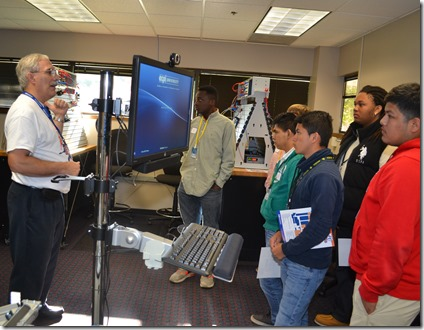 Philip Barone, an ECPI University instructor who oversees the mechatronics program, welcomes visiting high school students to the university's MFG Day Expo. (Photo by Bill Poovey)