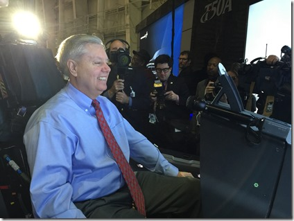 U.S. Sen. Lindsey Graham, R-S.C., takes instruction and begins to operate Lockheed Martin's T-50A flight simulator at the company's Greenville operations facility. (Photo by Matthew Clark)