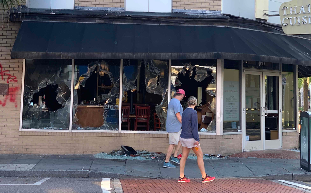 Passersby look at the damage to the windows of Basil Thai Cuisine on King Street in downtown Charleston on May 31. The damage occurred during social unrest the night of May 30 after the death of George Floyd, a black man, at the hands of Minneapolis police on May 25. (Photo/Shawnda Poynter)