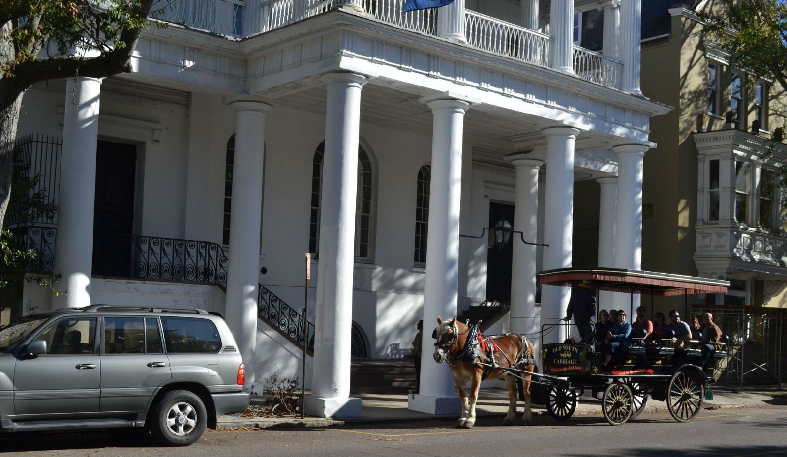A tour guide with Old South Carriage Co. talks to tourists outside the S.C. Society Hall on Meeting Street. (File Photo/Andy Owens)