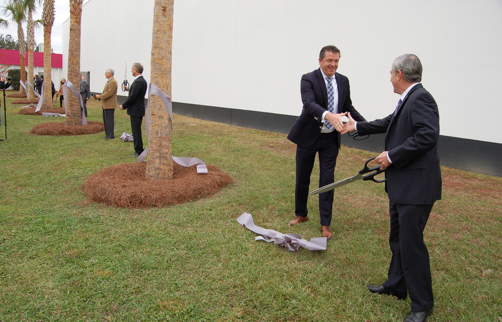 Executives, government officials and Kion Group employees simultaneously cut ribbons wrapping a line of seven palmetto trees outside the company's North American headquarters in Summerville. (Photo/Andy Owens)