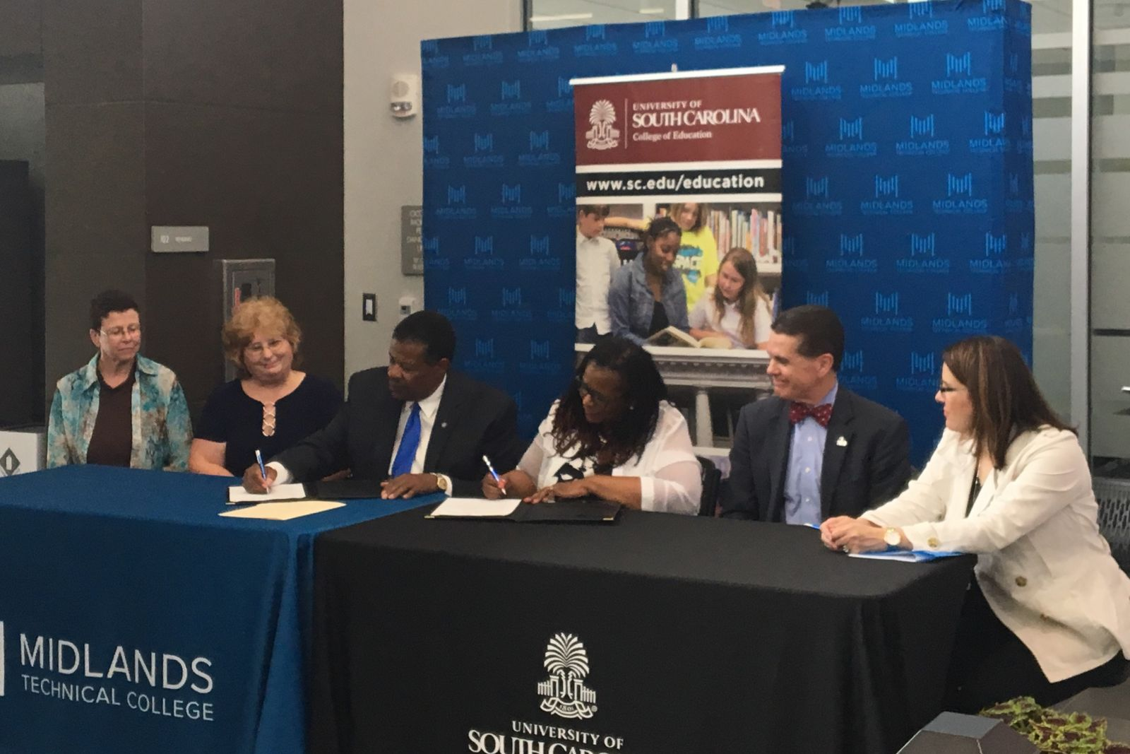 Officials from the University of South Carolina and Midlands Technical College, including MTC president Ron Rhames (third from left), sign an agreement to streamline the transfer process for MTC graduates looking to pursue an education degree at USC. (Photo/Melinda Waldrop)