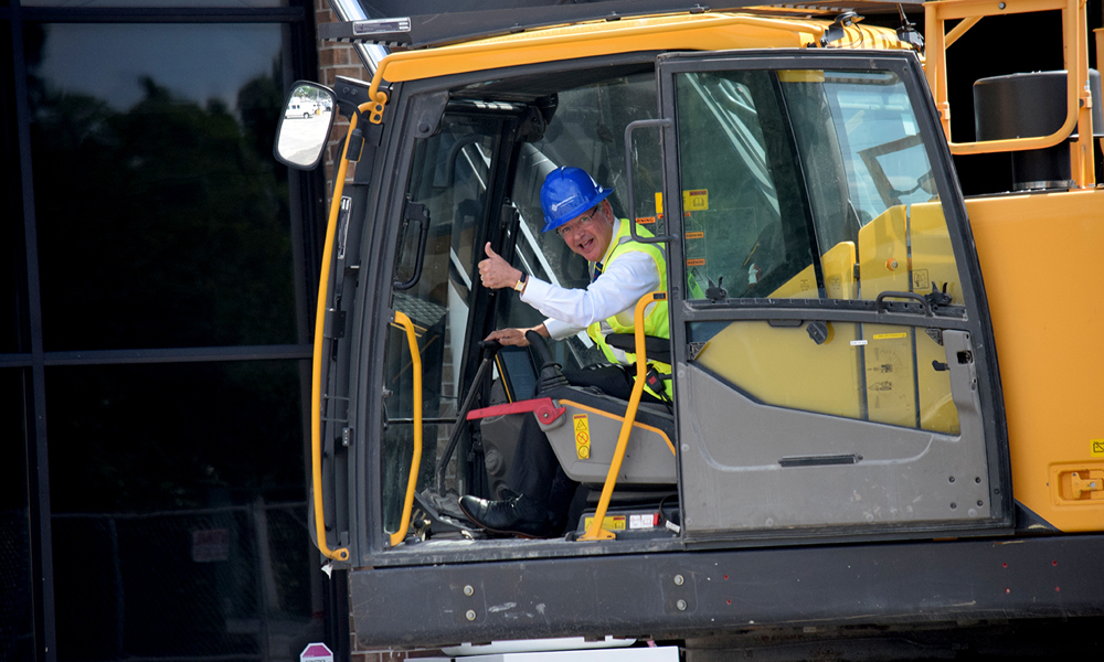 While Charleston Mayor John Tecklenburg seems completely comfortable behind the keyboard of a piano, he also seemed to relish this moment at the controls of an excavator on May 29 in West Ashley. (Photo/Patrick Hoff)