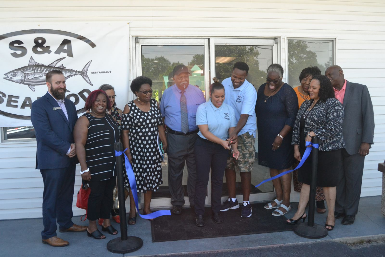 S&A Seafood celebrated the opening of a new location in North Columbia with a ribbon cutting on Friday. Co-owners Davant and Delilah Jenkins (center, with scissors) opened their first restaurant and market in Blythewood seven years ago. (Photo/Travis Boland)