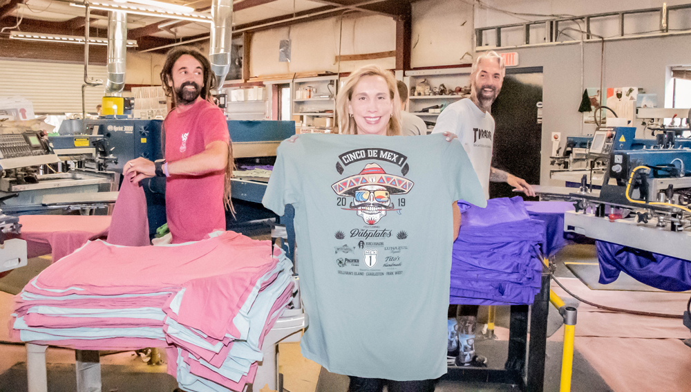 Owner Stephanie M. True displays one of Charleston Cotton Exchange's familiar t-shirt designs, flanked by printers Jacob Stackley (left) and William Colavita. Jacob and William have been with the company for more than 15 years.