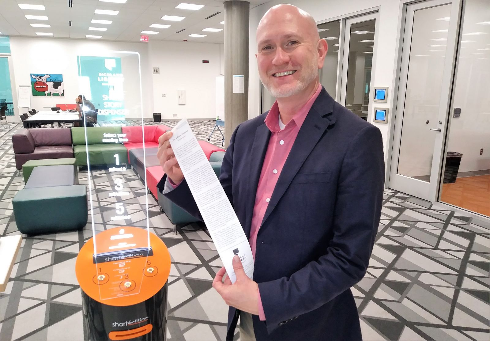 Tony Tallent, chief program and innovation officer at Richland Library, with the spoils from a short story dispenser.  (Photo/Travis Boland)