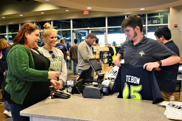 Columbia sisters Sarah Kate Calcutt, left, and Aimee Calcutt, buy Tebow T-shirts at the Fireflies gift shop. Clerk Justin Lindler, right, rings up the sale. (Photo/Chuck Crumbo)