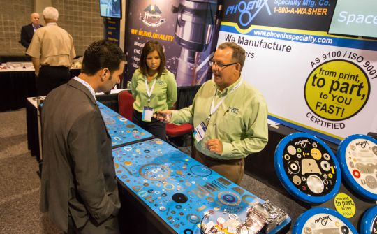 Phoenix Specialty sales manager Bob Smith, right, flanked by marketing assistant Allison Bird, talks with Geoff Caywood of General Dynamics during a visit at the company's booth during last month's S.C. Aerospace Conference in Columbia. (Photo/Chuck Crumbo)